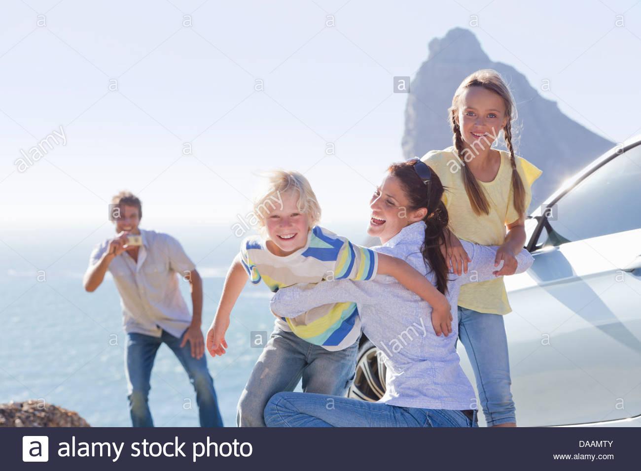 Playful family hugging outside car near ocean - Stock Image