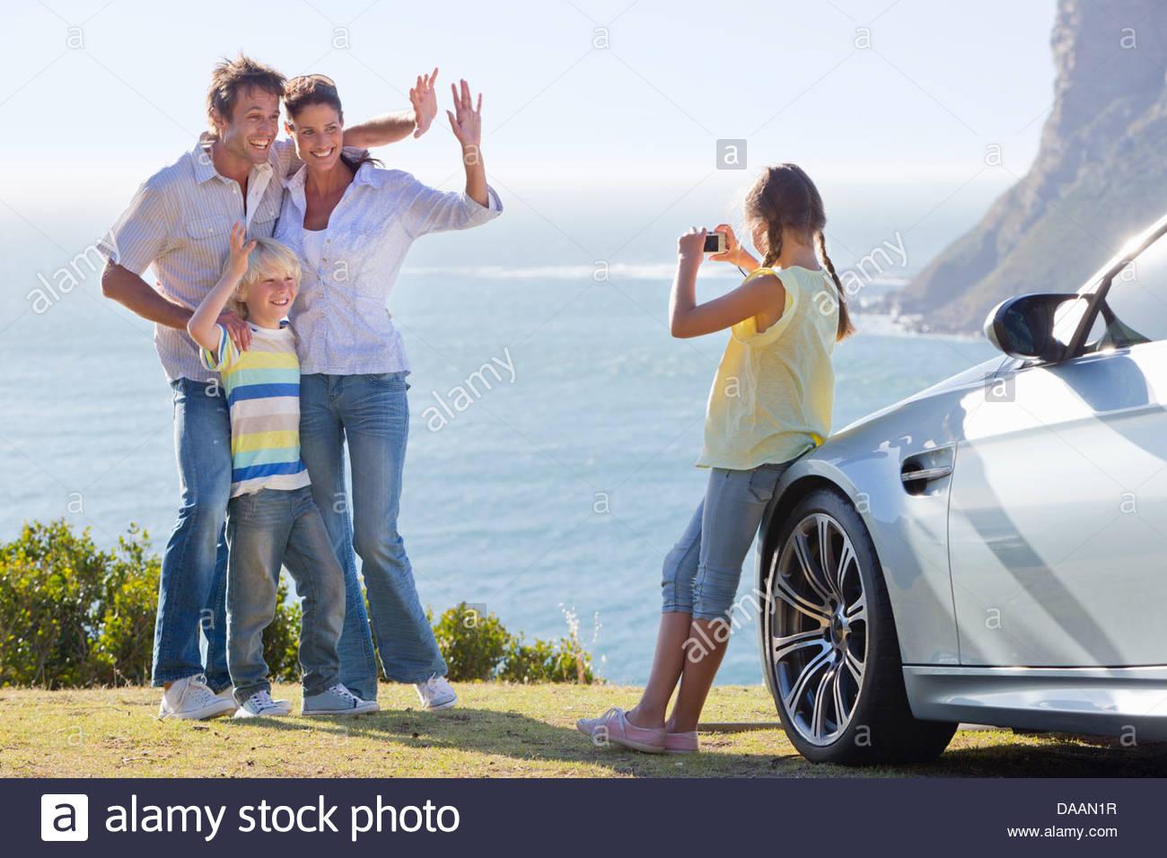Girl photographing waving family outside car near ocean - Stock Image