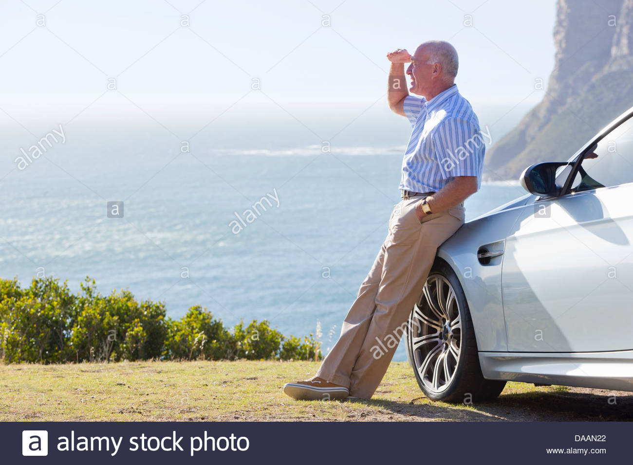 Man leaning against car and shielding eyes to look at ocean view - Stock Image