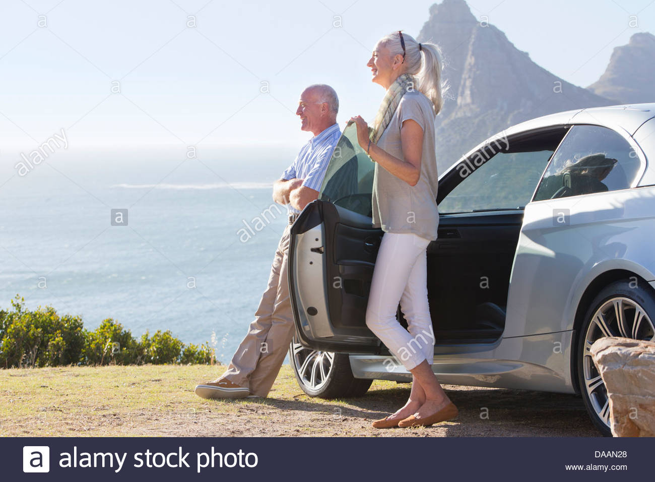 Smiling couple looking at ocean view outside car - Stock Image