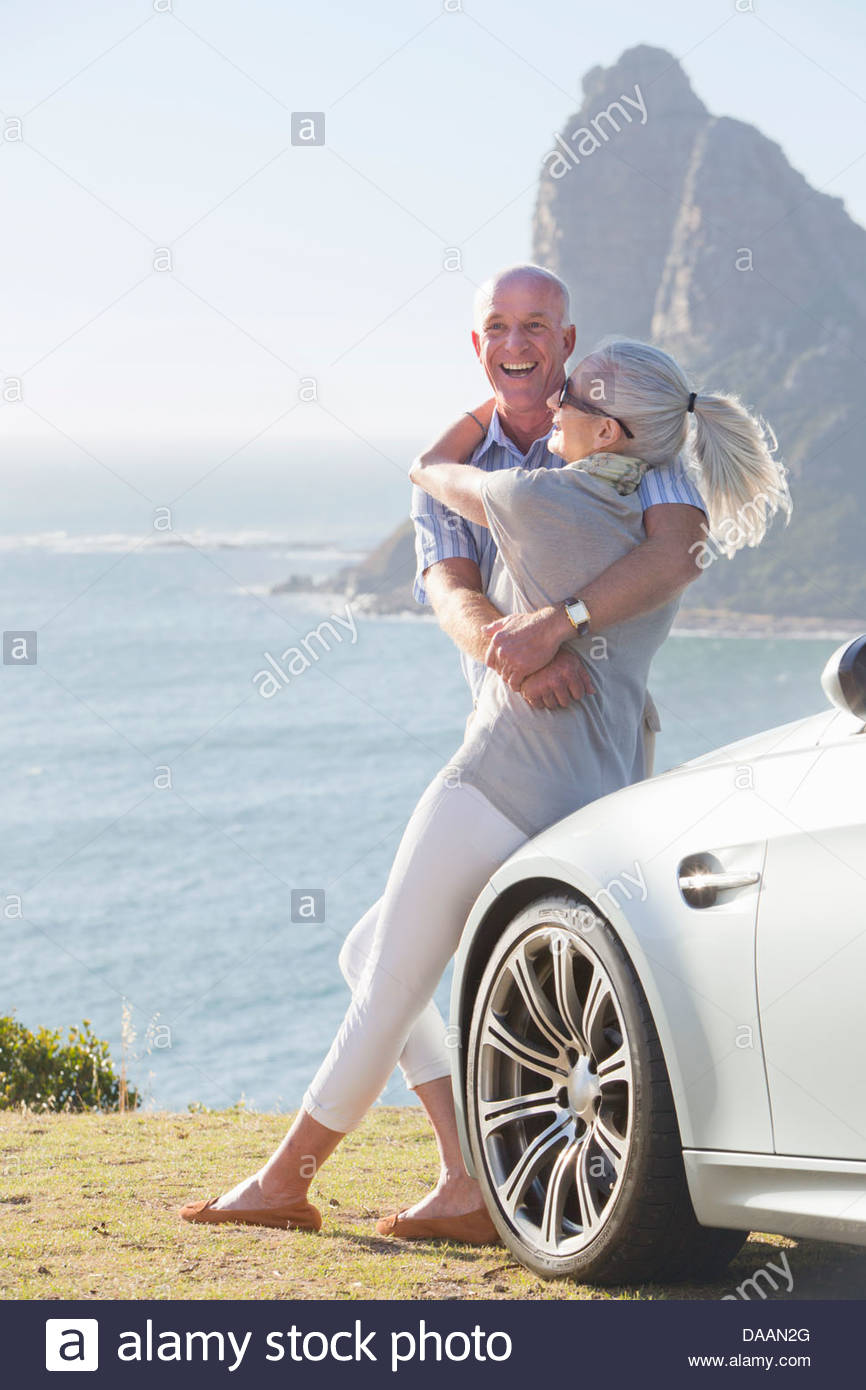 Enthusiastic couple hugging outside car near ocean - Stock Image