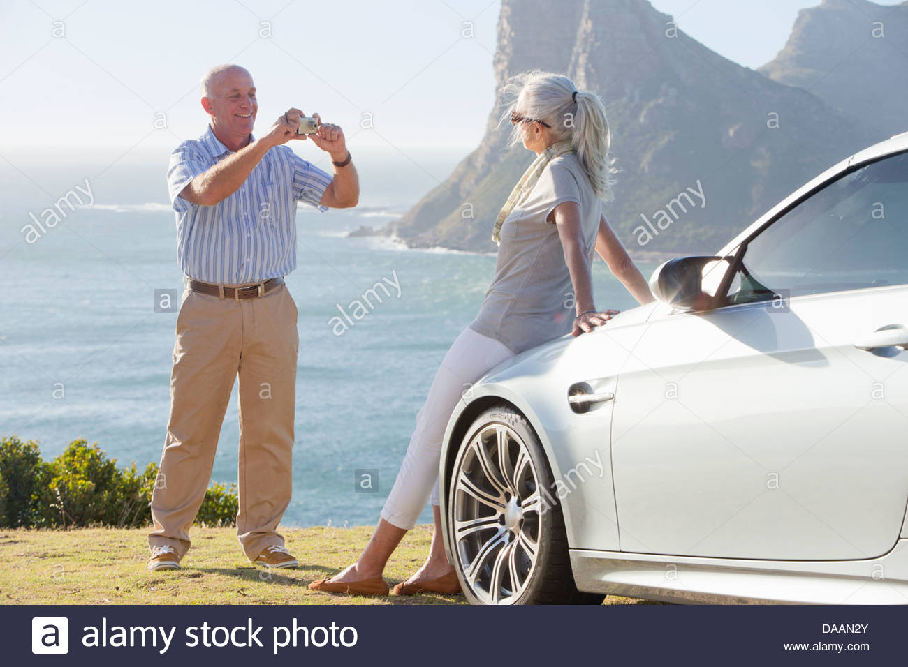 Man photographing woman leaning against car near ocean - Stock Image