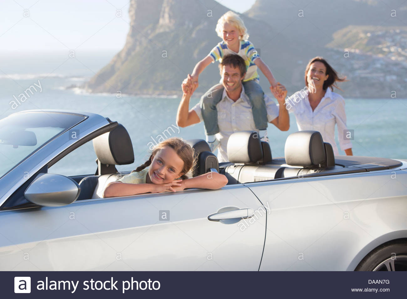 Portrait of happy family with convertible near ocean - Stock Image