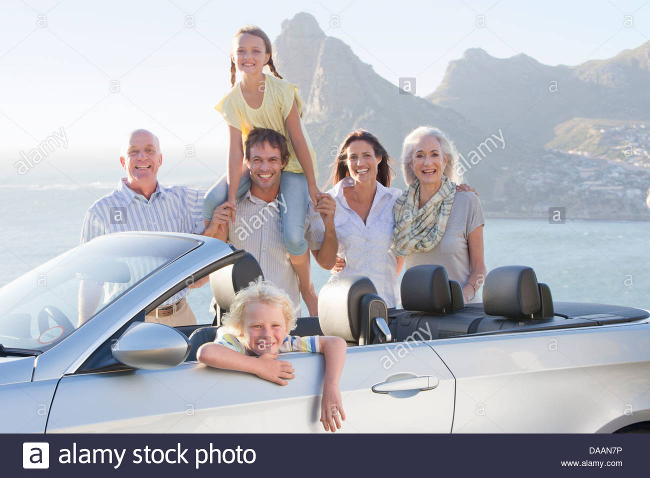 Portrait of happy multi-generation family with convertible near ocean - Stock Image