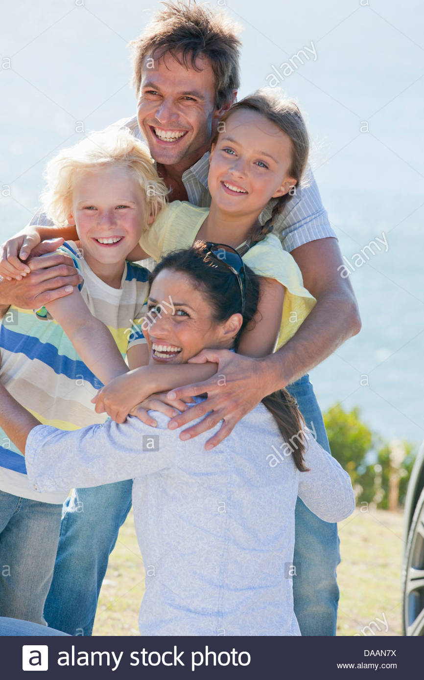 Portrait of enthusiastic family hugging - Stock Image