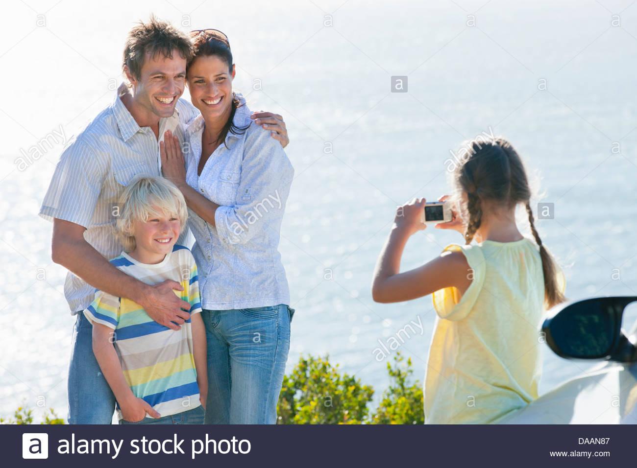 Girl photographing family near ocean - Stock Image