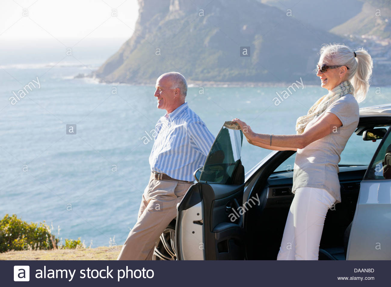Couple looking at ocean view outside car - Stock Image