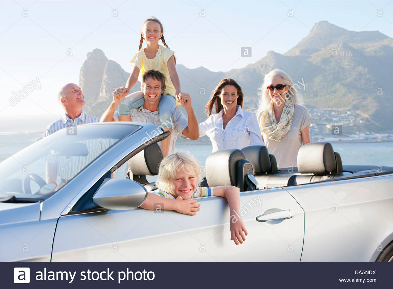 Portrait of smiling boy in convertible with multi-generation family and ocean in background - Stock Image