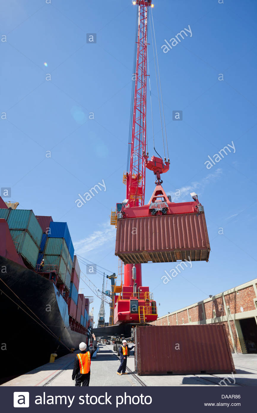 Worker guiding crane unloading container ship at commercial dock - Stock Image