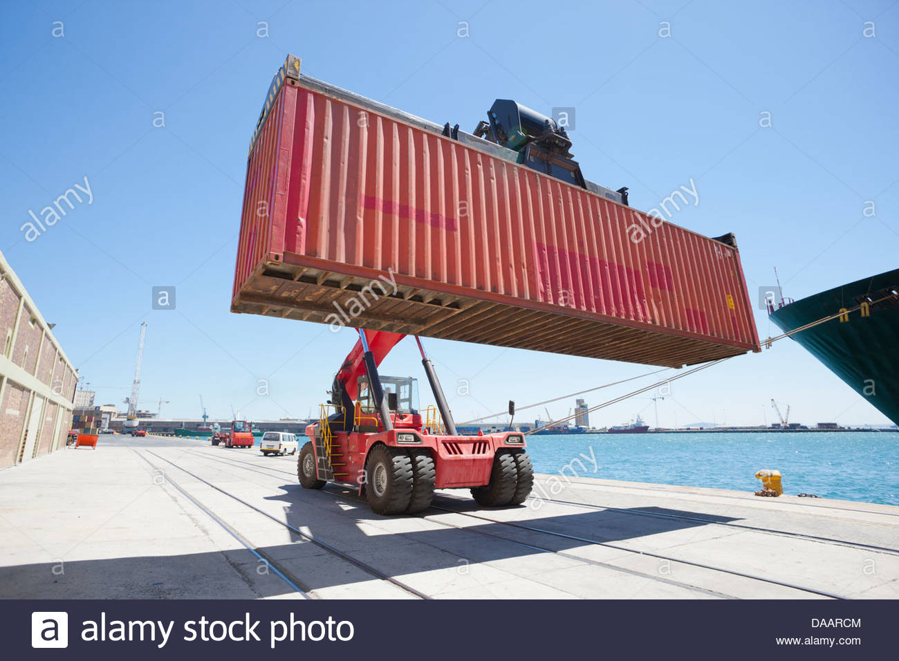 Mobile crane moving container ship at commercial dock Stock Photo