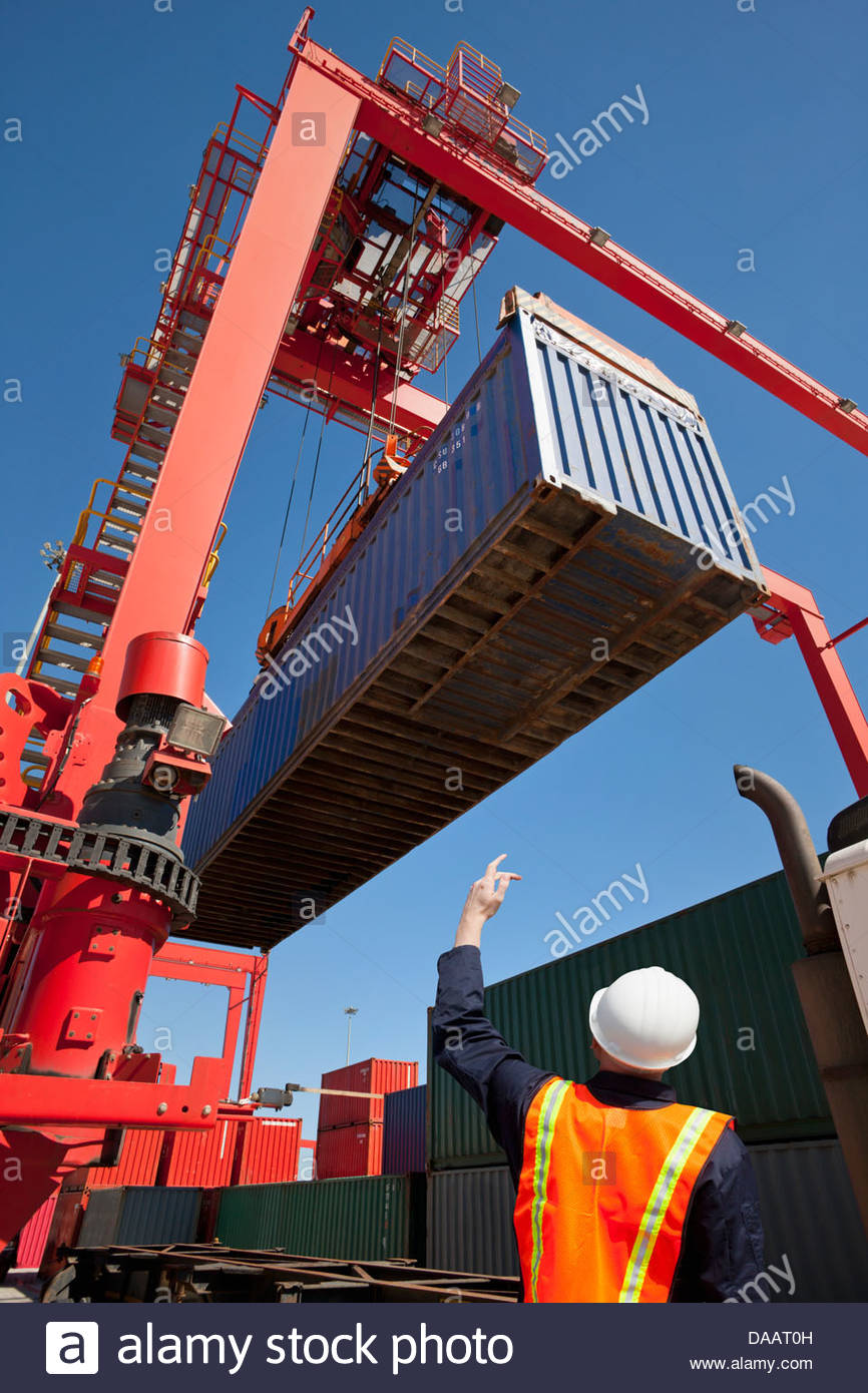 Worker guiding crane lifting cargo container at commercial dock - Stock Image