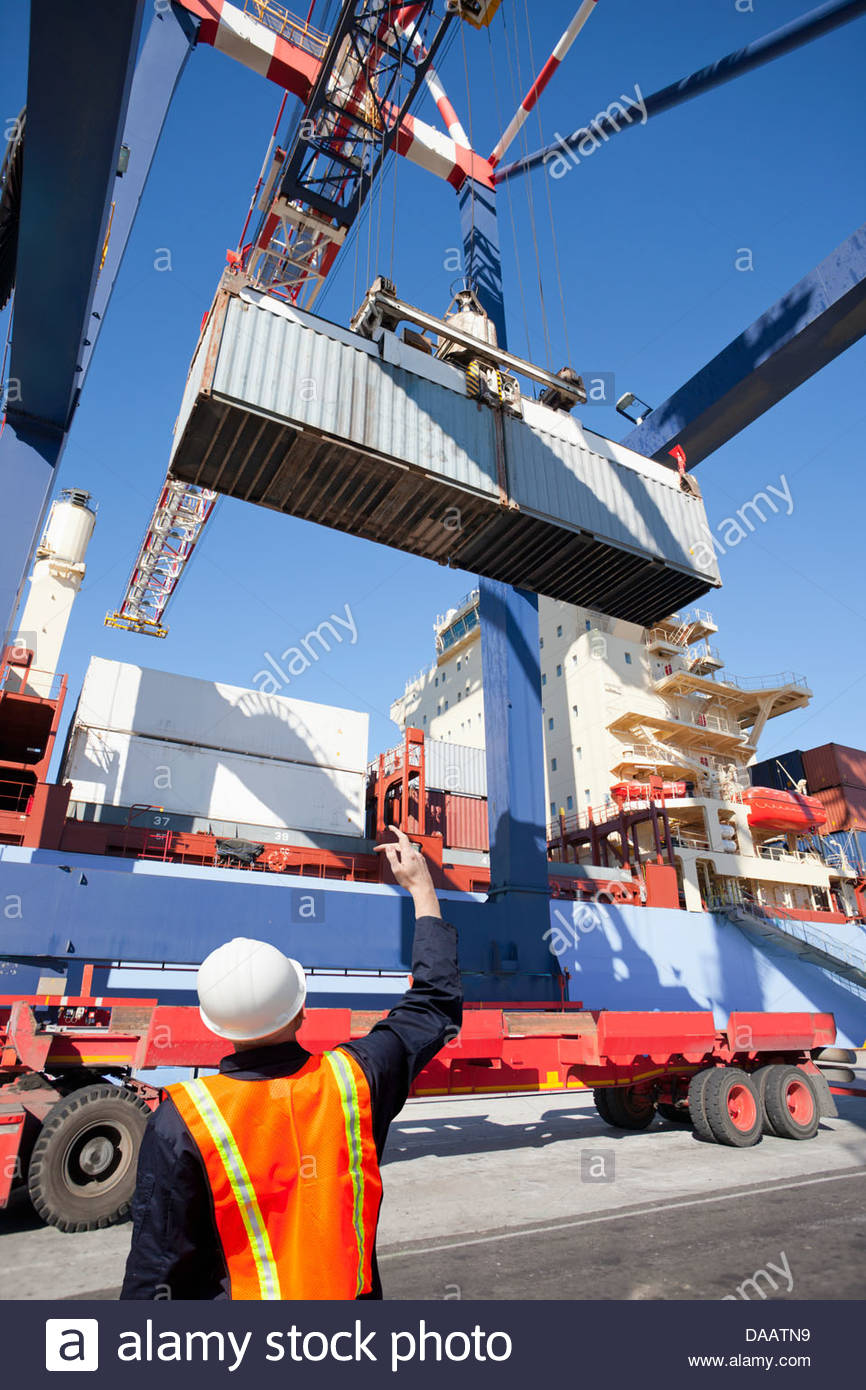 Worker guiding crane with cargo container at commercial dock Stock Photo