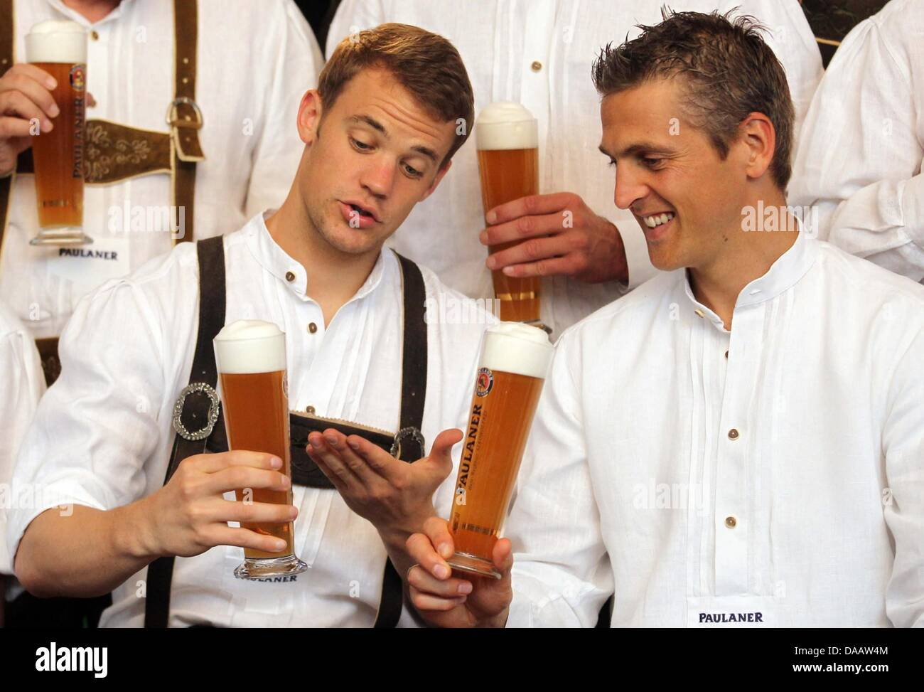 FC Bayern Munich s Manuel Neuer and Joerg Butt wear lederhosen and drink  beer during a sponsorship appointment in Munich 606725e4f