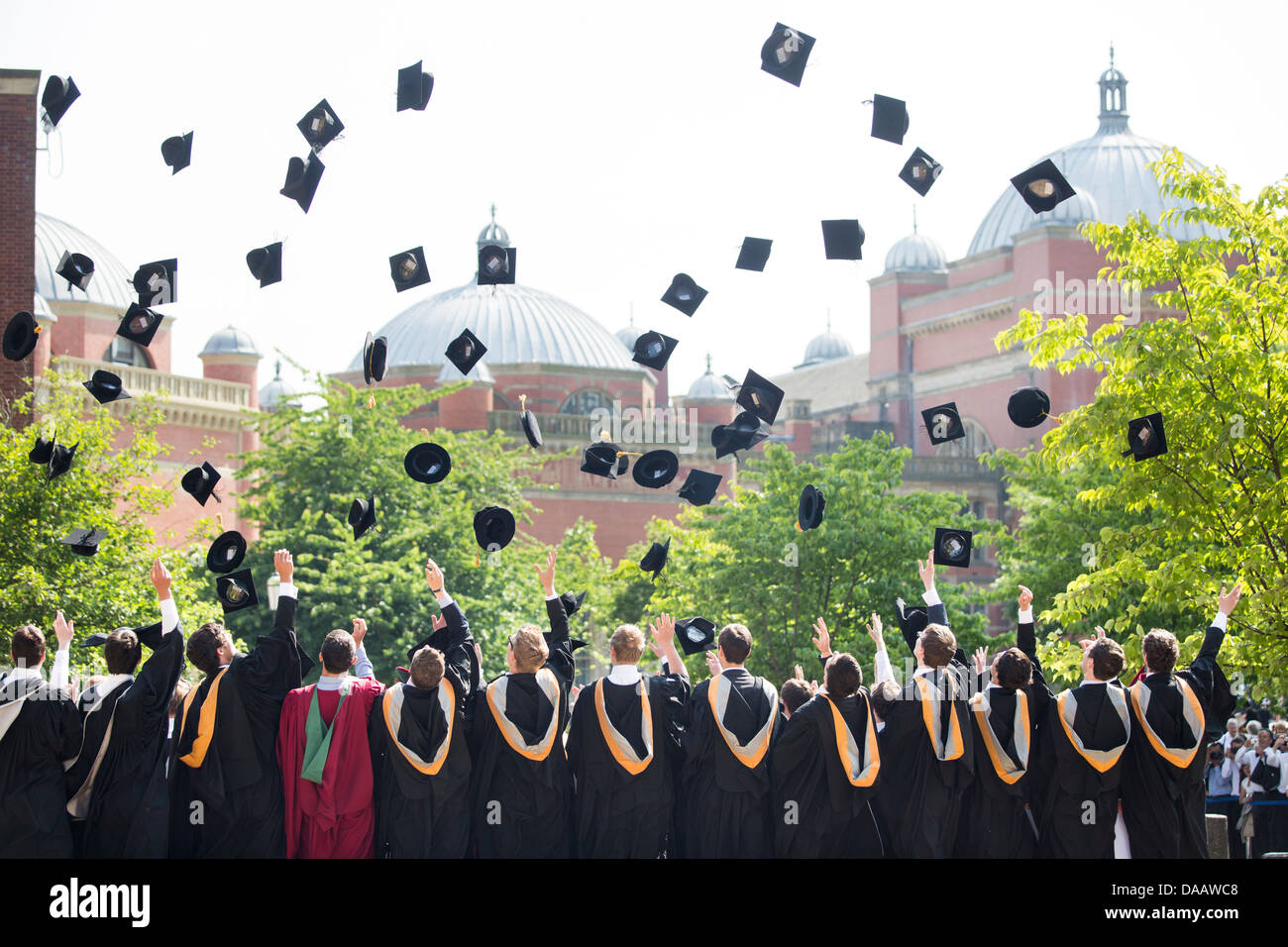 Graduates throw their caps in the air at Birmingham University, UK, after the graduation ceremony. - Stock Image