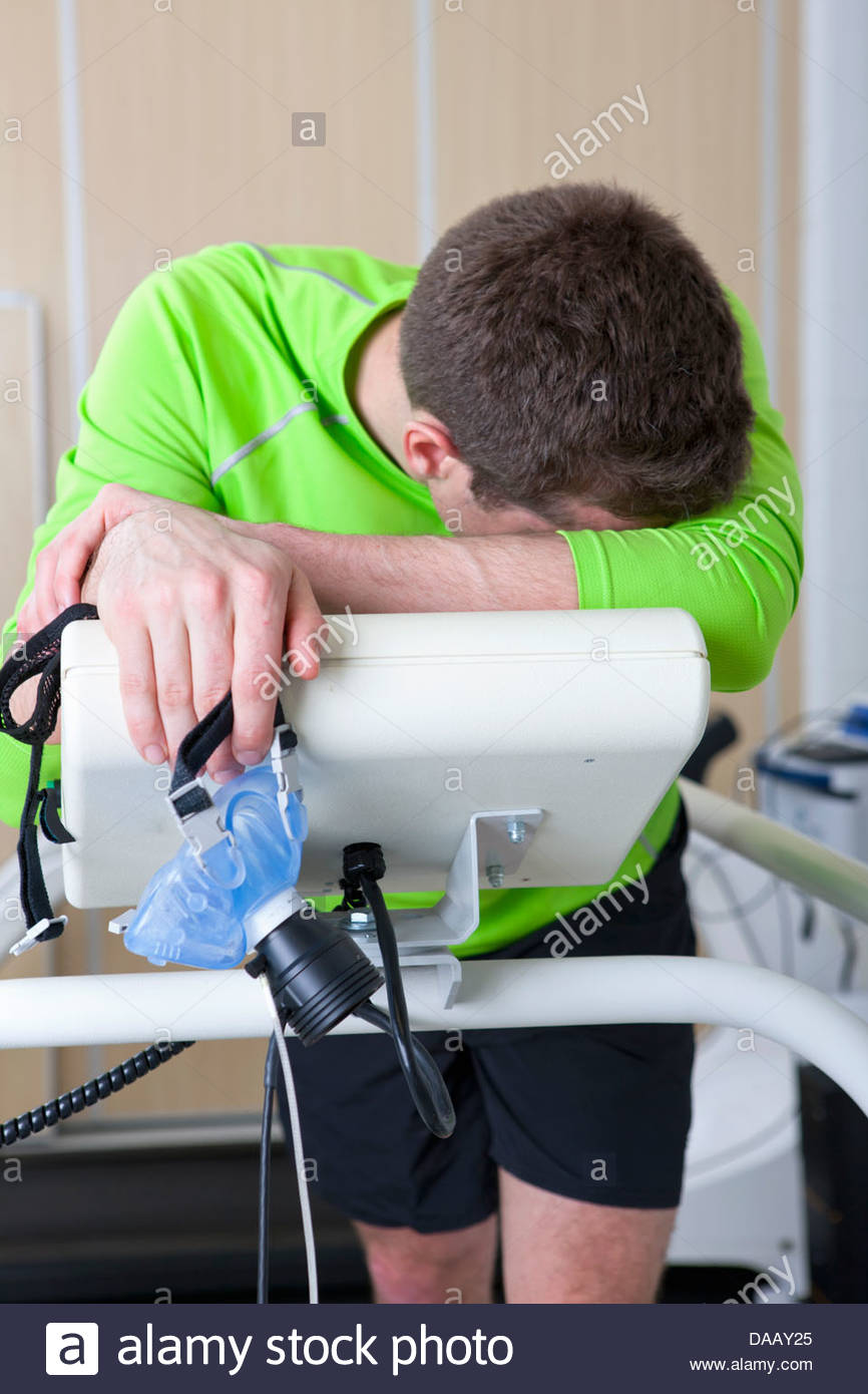 Tired runner with head in hands holding mask and leaning on treadmill in sports science laboratory - Stock Image