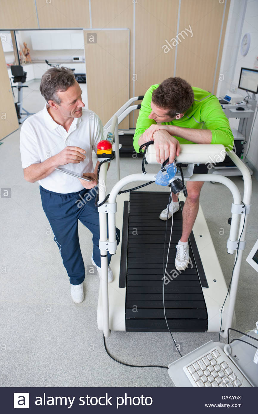 Sports scientist talking to runner with mask on treadmill in laboratory - Stock Image