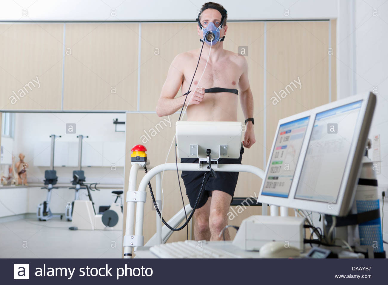 Runner with mask on treadmill in sports science laboratory - Stock Image