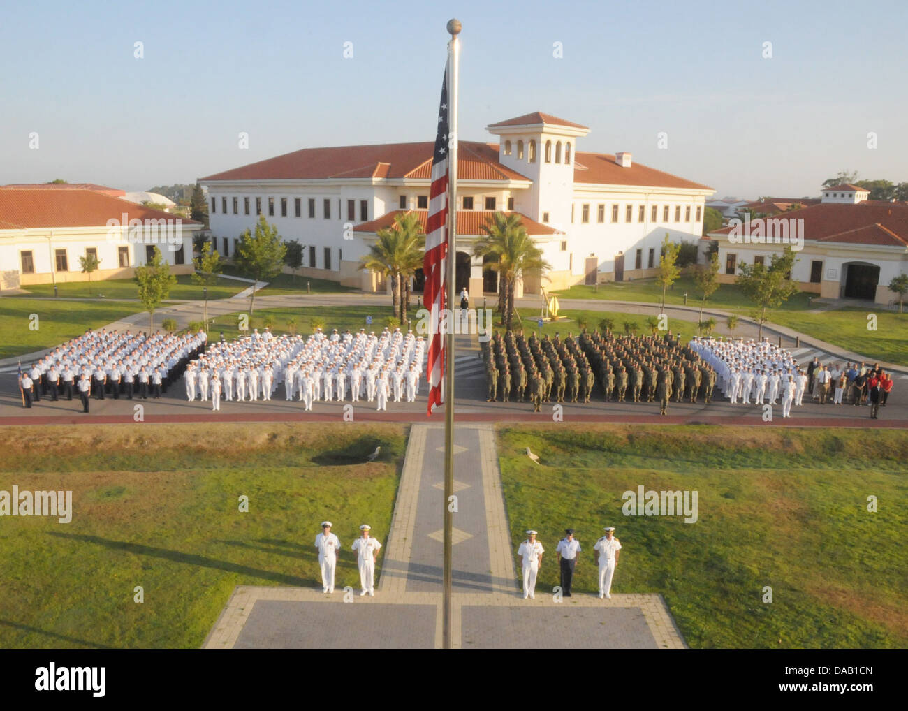 Service members and civilian employees assigned to Naval Station Rota, Spain, stand at attention during the annual - Stock Image