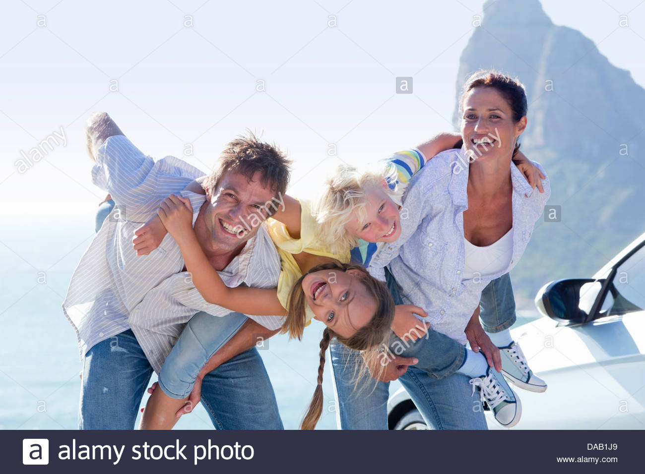 Portrait of happy family next to car with ocean in background - Stock Image