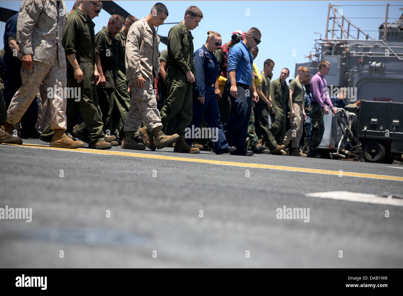 Sailors and Marines conduct a foreign object debris (FOD) walkdown aboard the amphibious assault ship USS Kearsarge - Stock Image