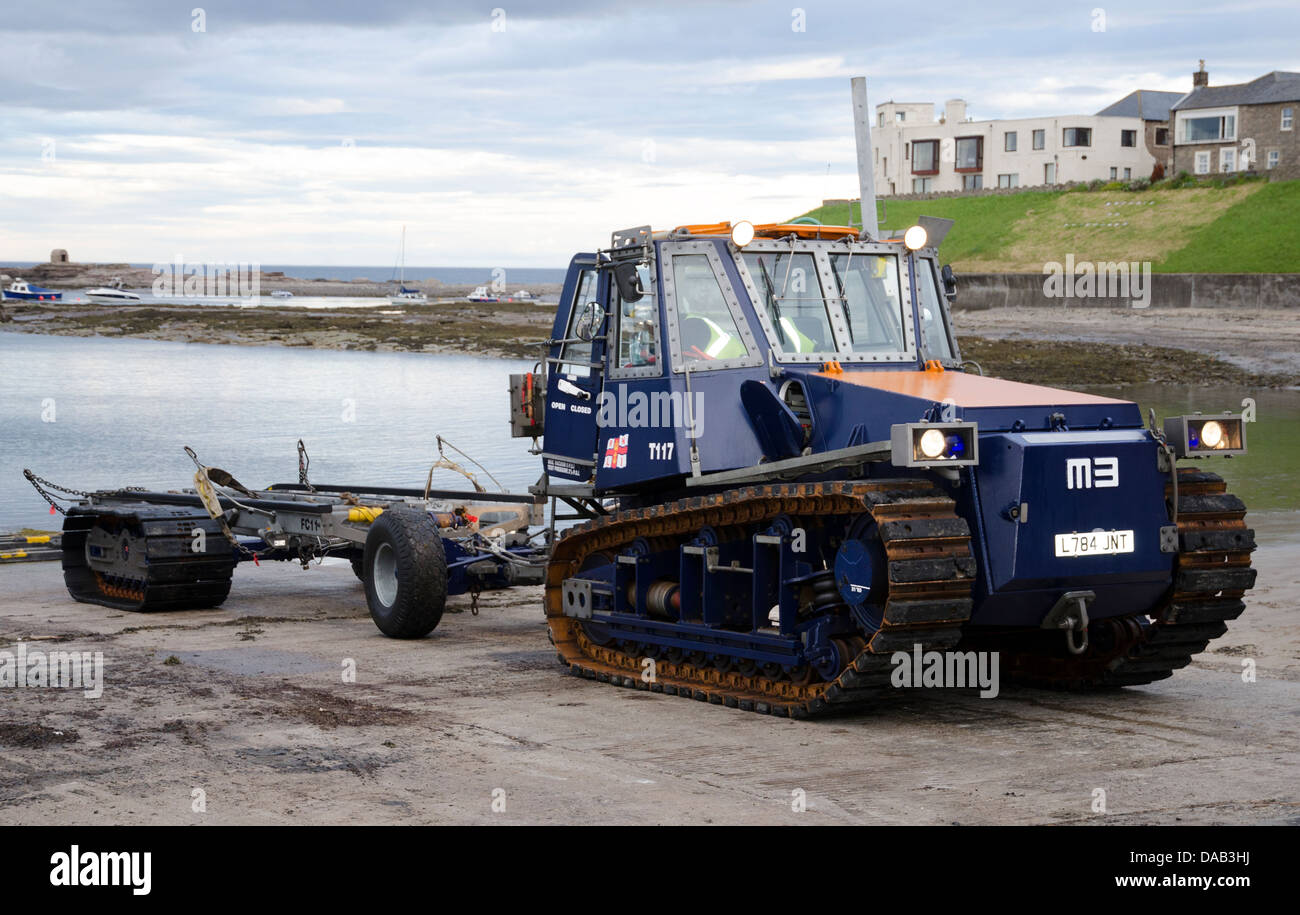 RNLI tracked vehicle waiting to recover lifeboat grace darling after practice operation seahouses harbour northumberland - Stock Image