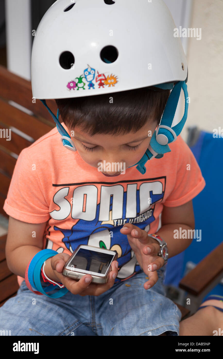 Boy,six years old,wearing a bicycle helmet,uses a touch screen mobile phone Stock Photo