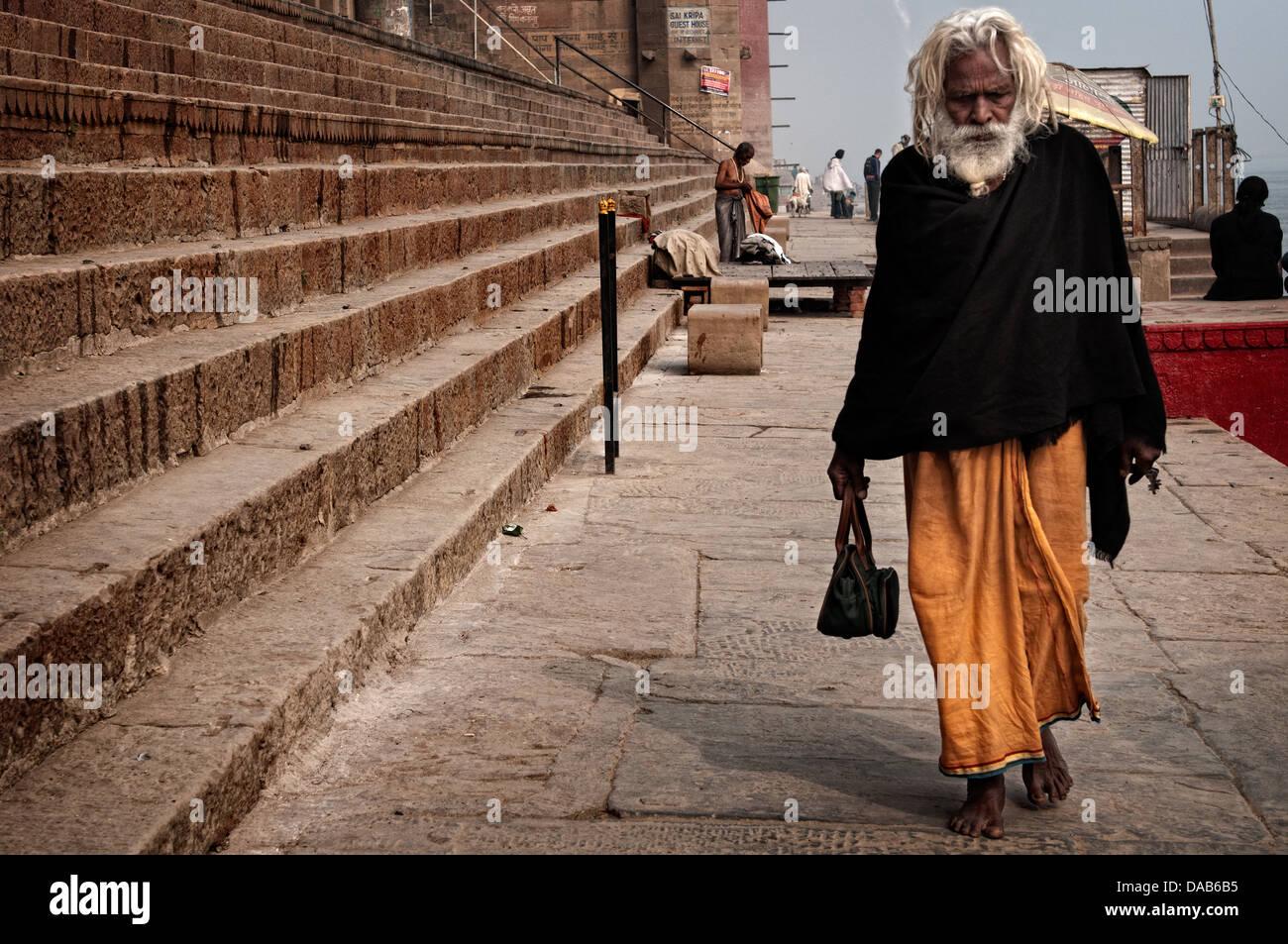 Sadhu walking on the ghats. Varanasi, Benares, Uttar Pradesh, India - Stock Image