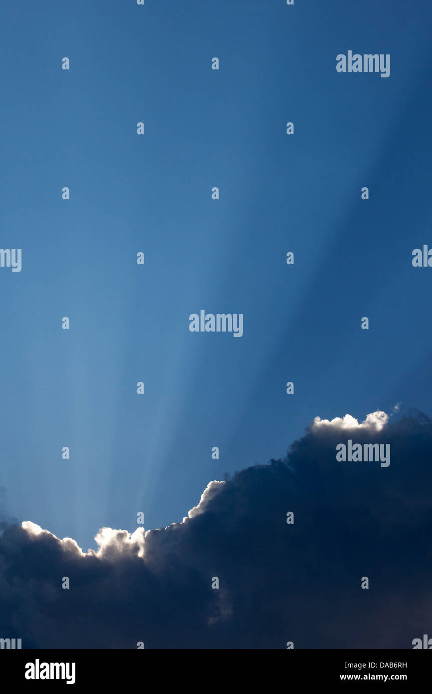 Crepuscular rays shining up from dark cloud after rainstorm - Stock Image