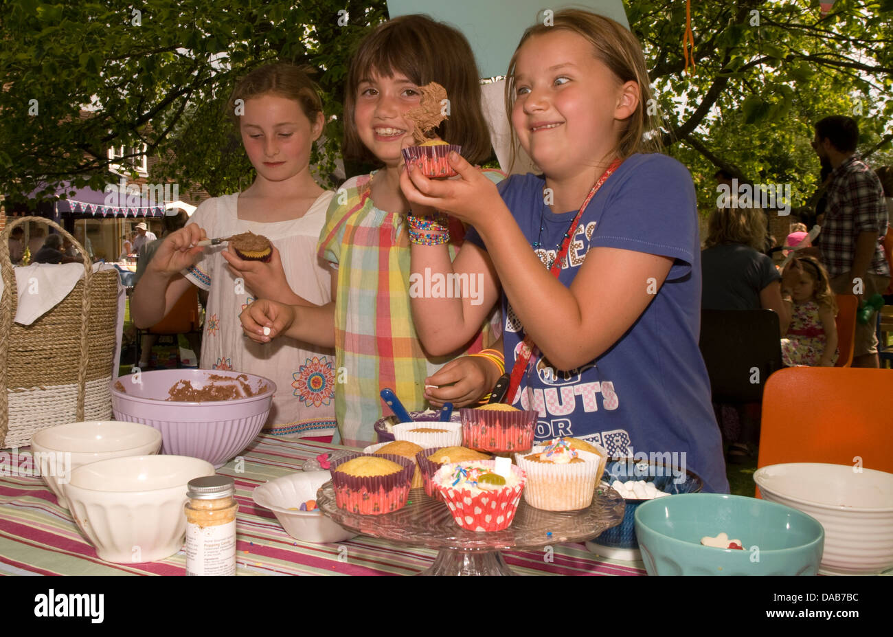 Youngsters at cake stall decorating/icing their own cake at a summer fete, East Meon, Hampshire, UK. Stock Photo