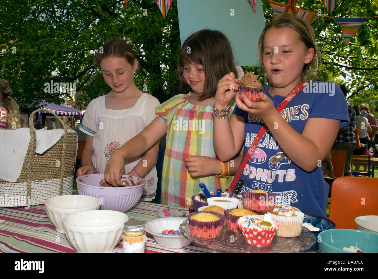 Youngsters at cake stall decorating/icing their own cake at a summer fete, East Meon, Hampshire, UK. - Stock Image