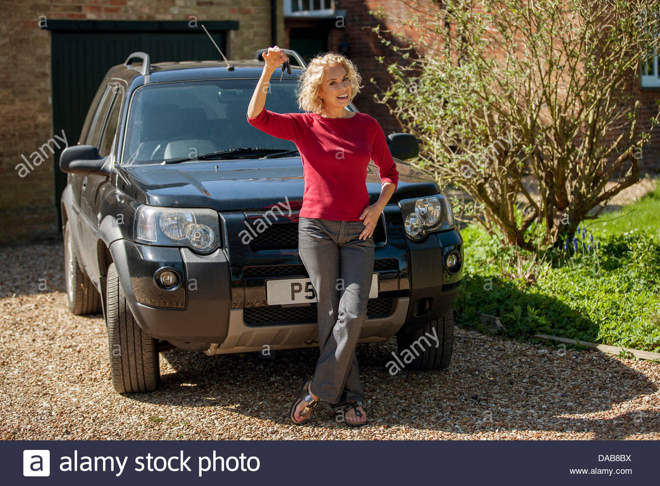 A mature woman holding the keys to her new car - Stock Image