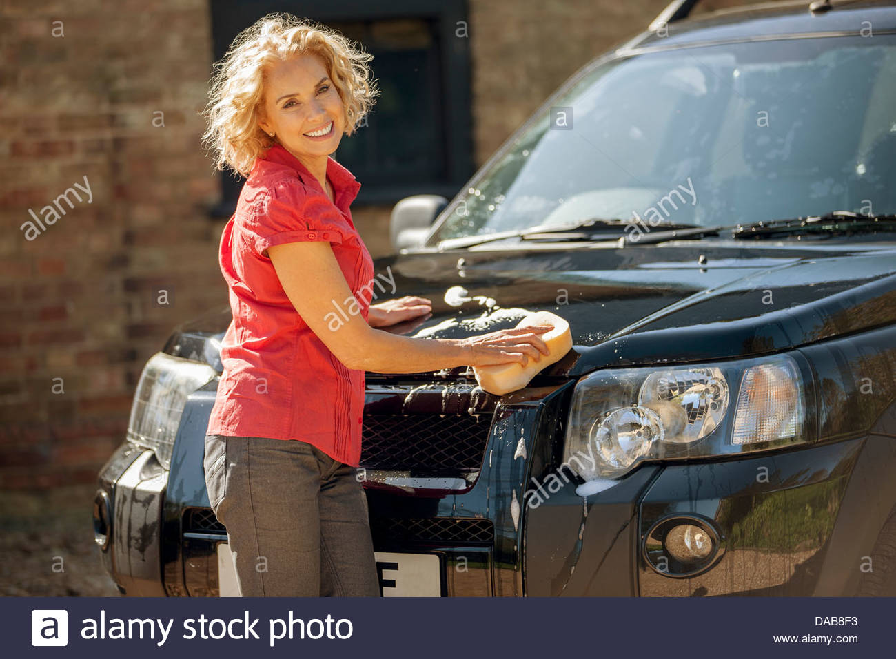 A mature woman washing a four wheel drive car - Stock Image