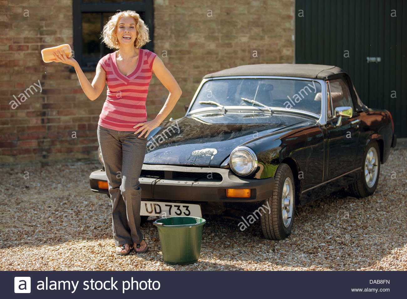 A mature woman washing a classic sports car - Stock Image