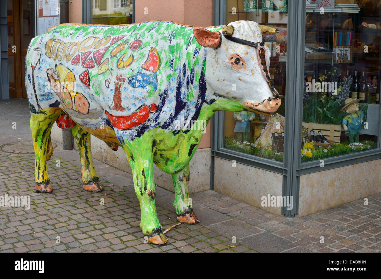 Life size painted model of a cow outside a Swiss butcher's shop - Stock Image
