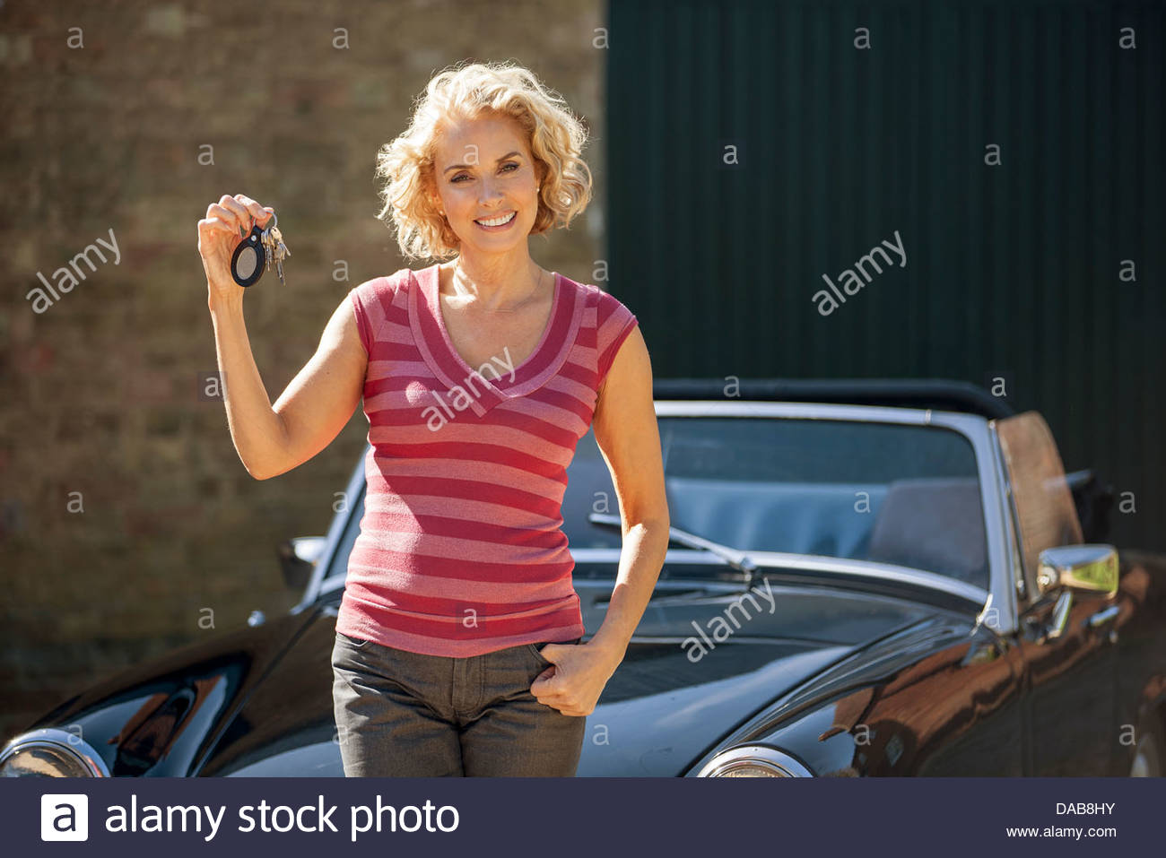 A mature woman holding the keys to classic sports car - Stock Image
