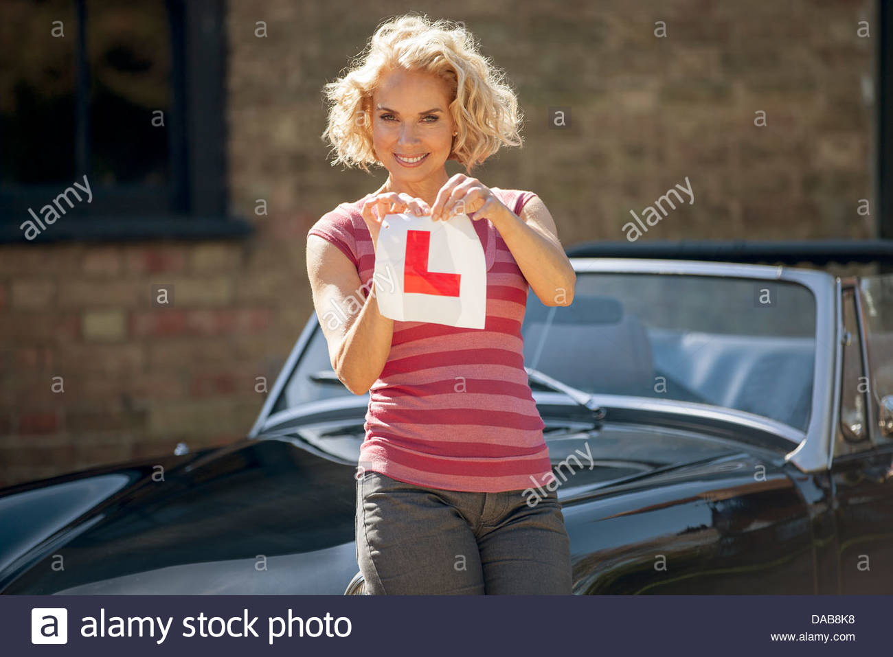 A mature woman tearing up a learner driver plate - Stock Image