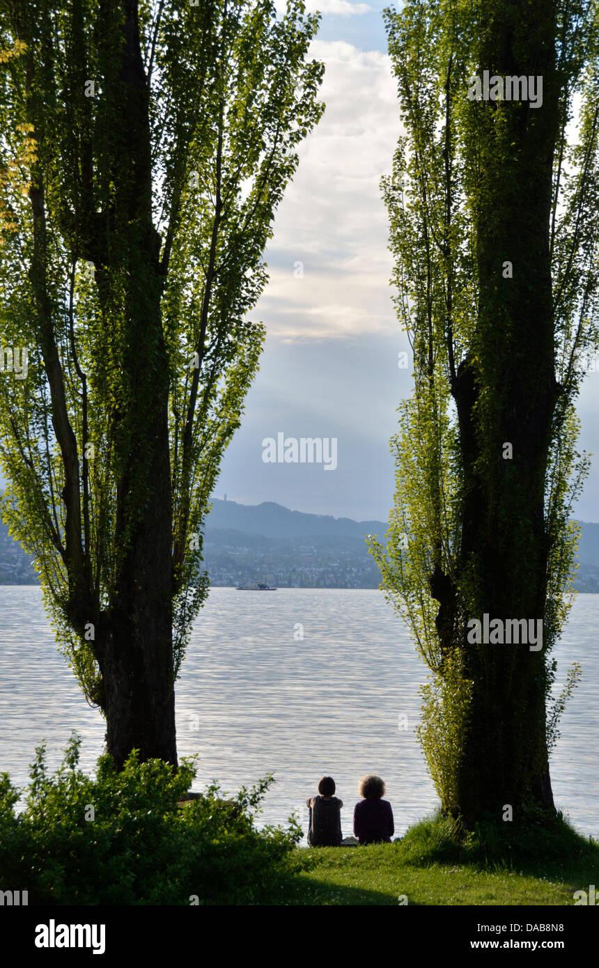 Two women sitting next to Lake Zurich at Au, Switzerland - Stock Image