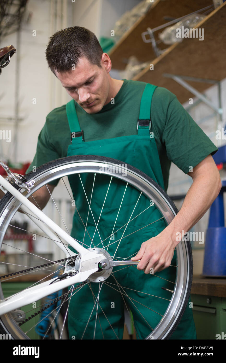Mechanic or serviceman installing wheel on a bicycle in workshop - Stock Image