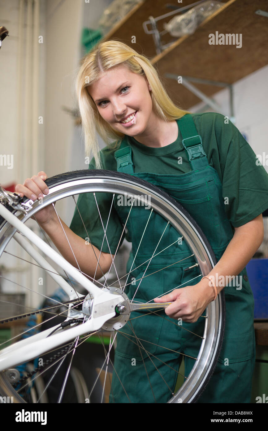 Female mechanic in workshop installing or repairing a bicycle wheel - Stock Image