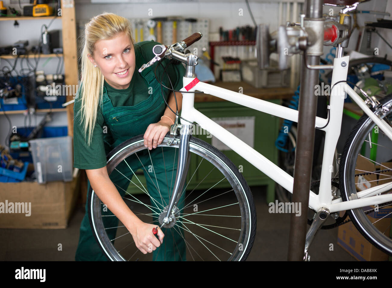 Bicycle mechanic repairing tyre or wheel on bike in a workshop - Stock Image