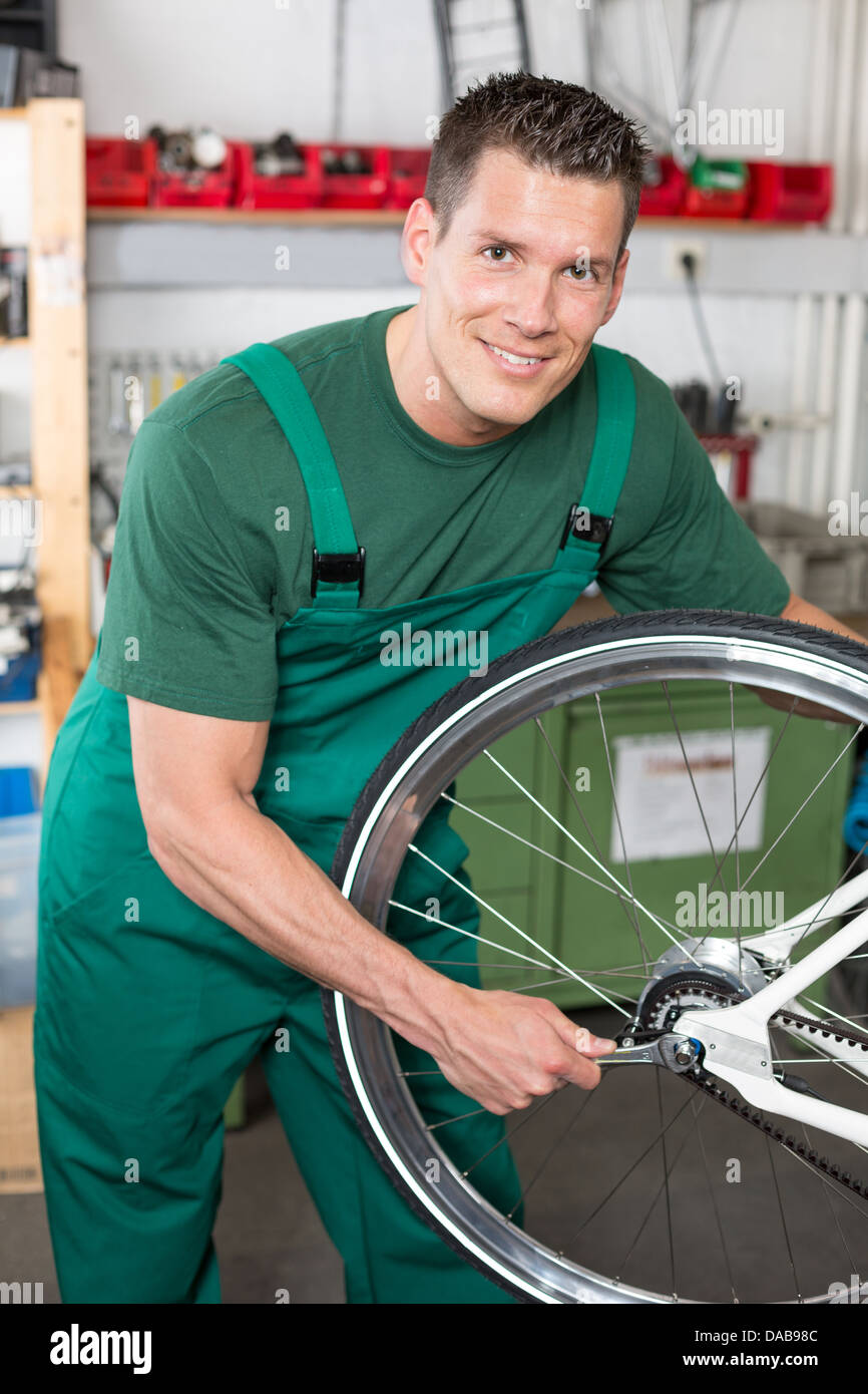 Bicycle mechanic with wrench changing wheel on bike in workshop - Stock Image