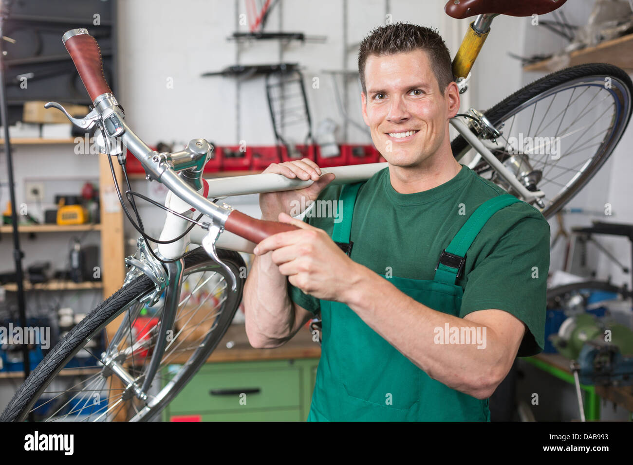 Bicycle mechanic carrying a bike in workshop smiling into the camera - Stock Image
