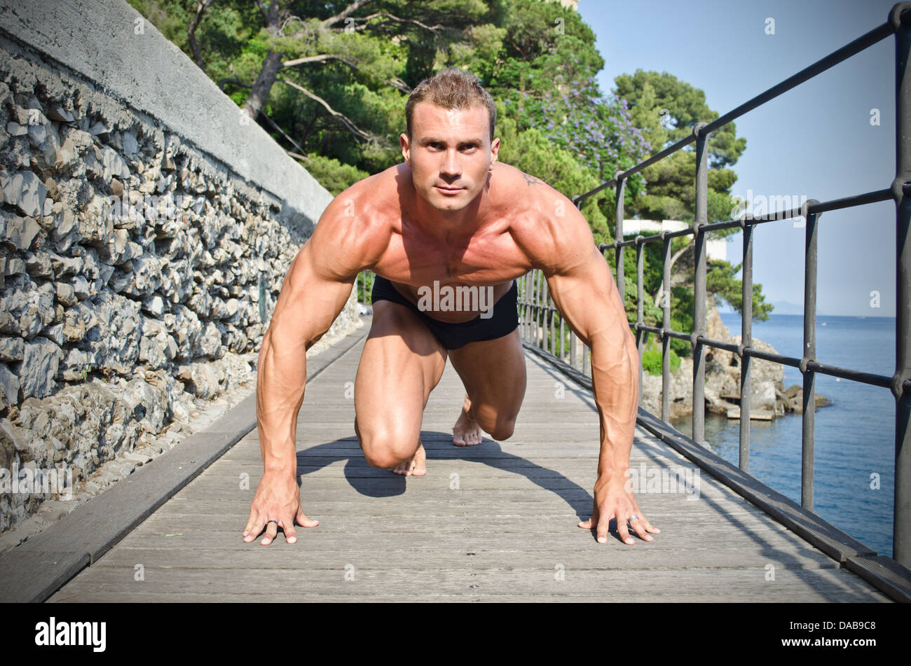 Young, handsome bodybuilder ready to sprint and run, outdoors - Stock Image