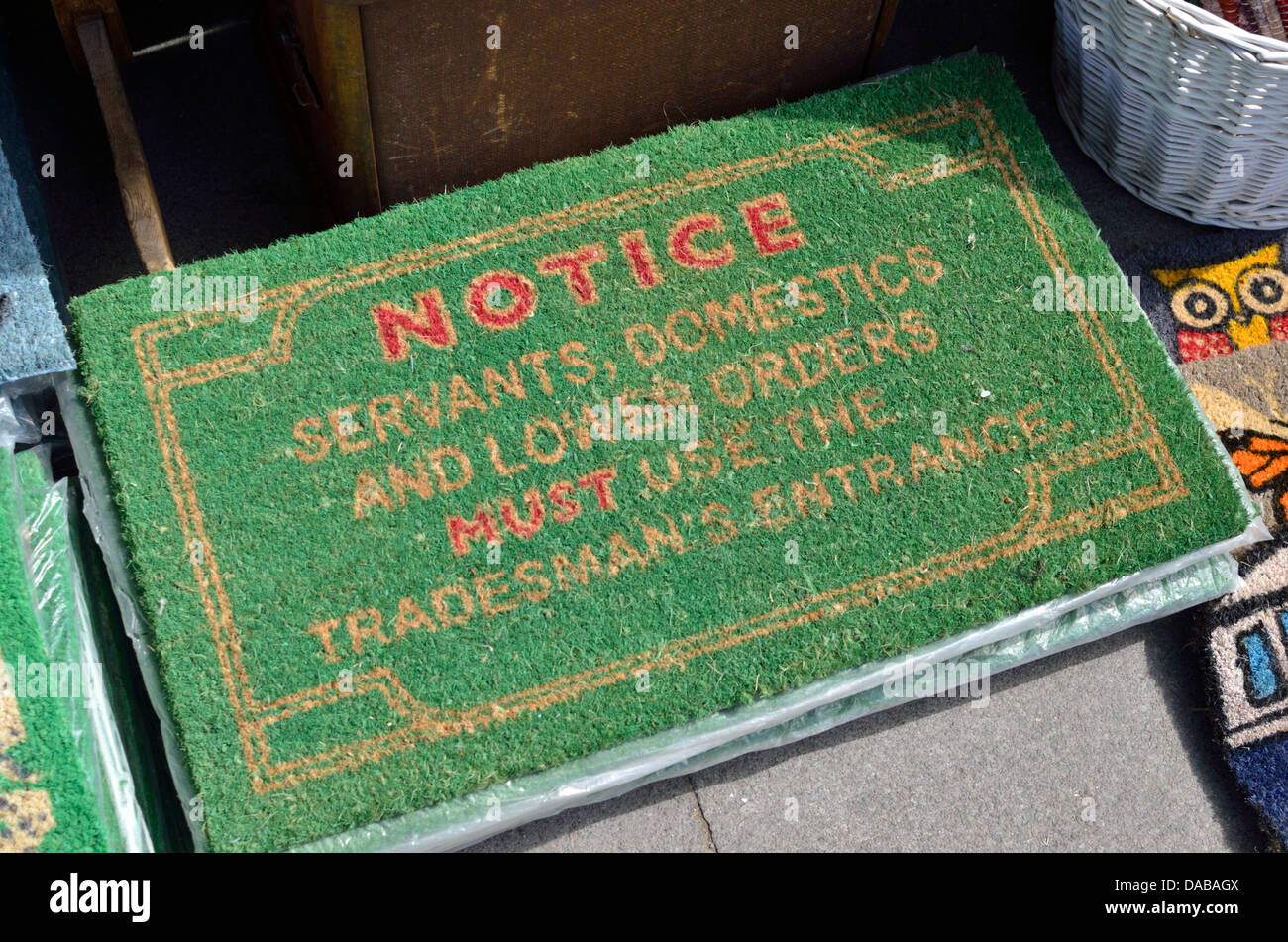 A UK doormat containing a notice to servants, domestics and lower orders to use the tradesman's entrance - Stock Image