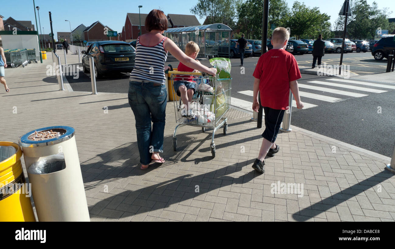 Mother and kids with a shopping trolley of groceries outside Morrisons supermarket carpark walking to the car Wales - Stock Image