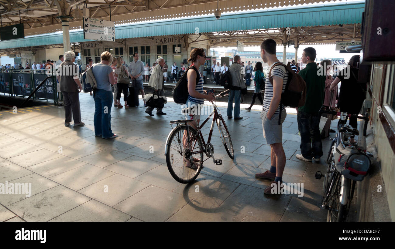 Passengers cyclists with bikes in summer awaiting train on Cardiff Central Railway Station platform in Wales UK - Stock Image