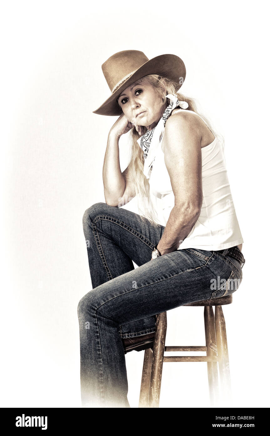 Woman rancher sitting on a stool with a cowboy hat and scarf. Antiqued and faded - Stock Image