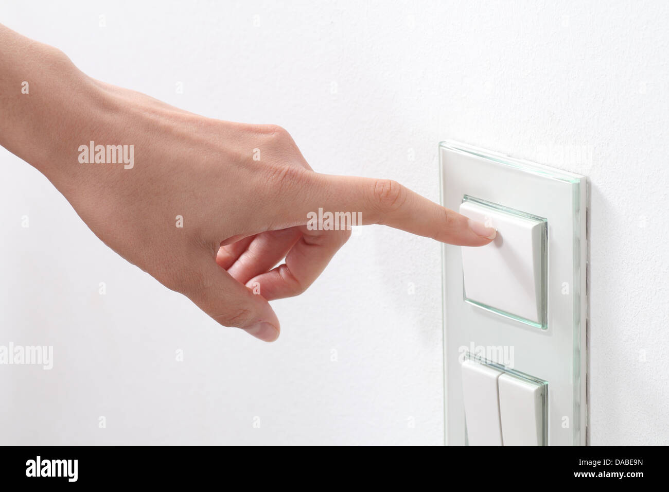 Woman hand turning on the light with a wall switch - Stock Image