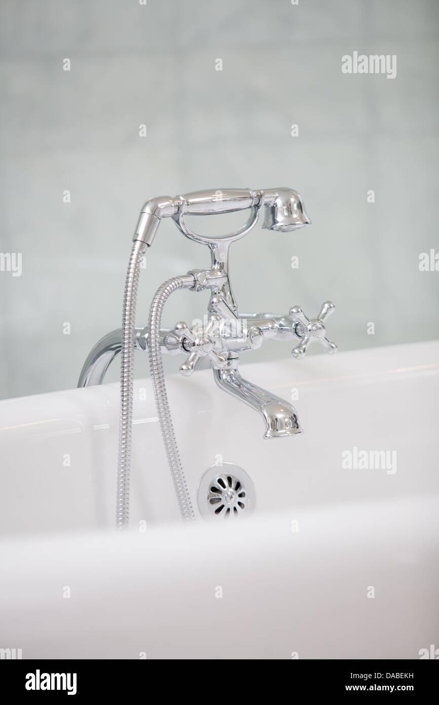 A bathroom fixture on the side of a bathtub. - Stock Image