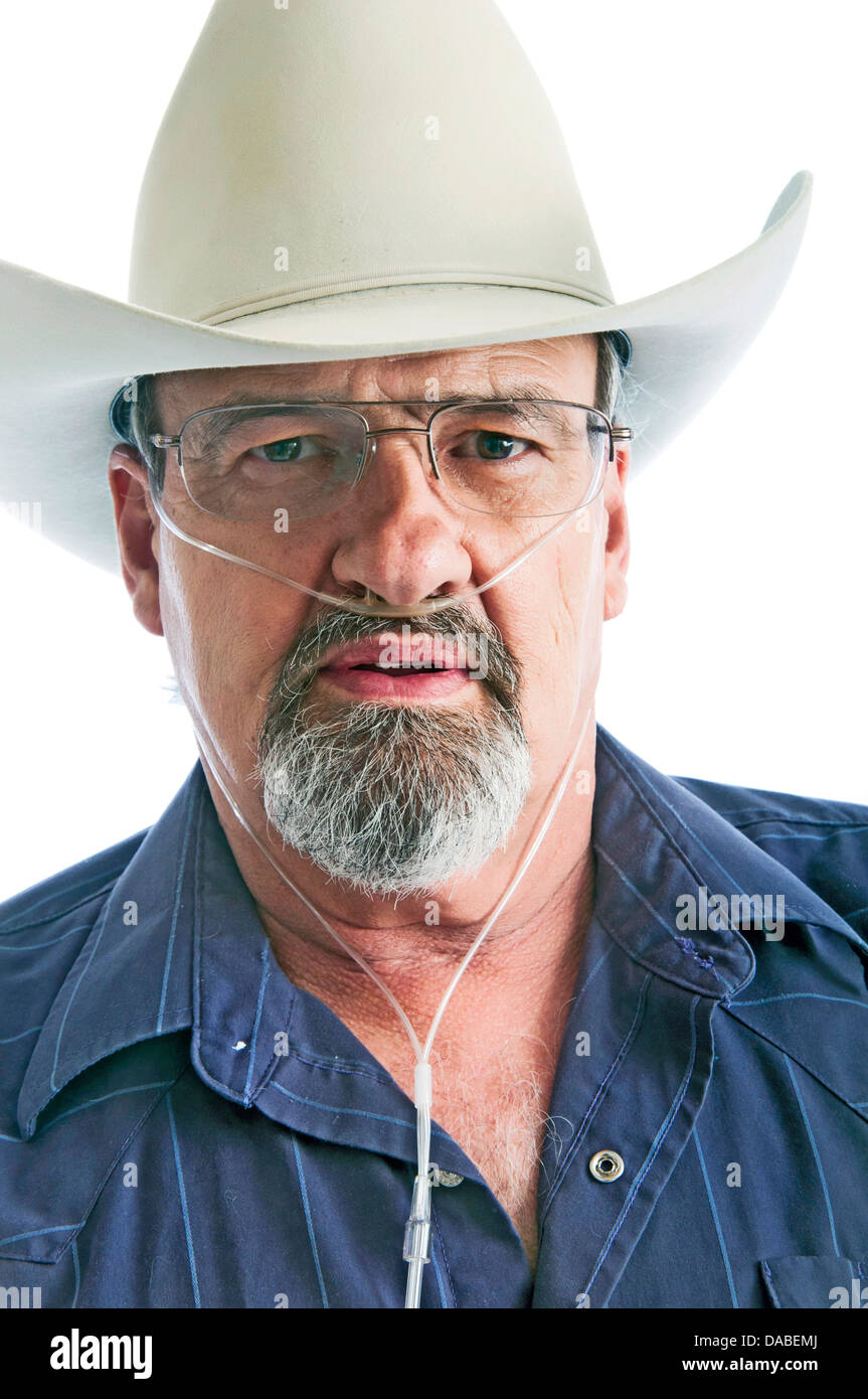 Mature cowboy with a breathing disability, wearing an Oxygen cannula and eyeglasses. - Stock Image